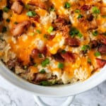 white casserole dish with a twice baked cauliflower with bacon, cheese, and green onions