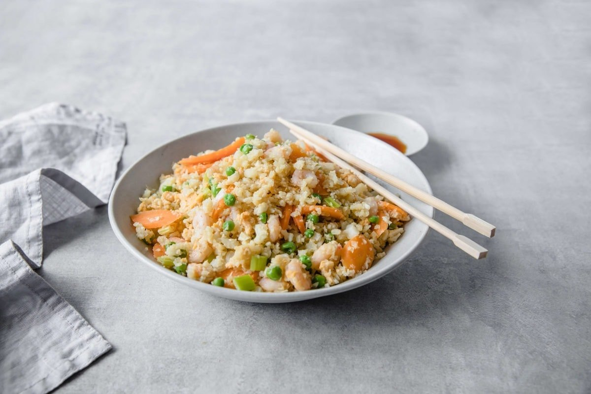A shallow bowl filled with Shrimp Fried Cauliflower Rice, accented with carrots, peas, and green onions with chopsticks and side of extra coconut aminos.