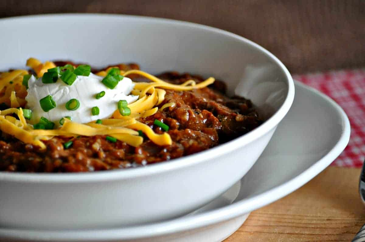 a closeup of a bowl of chili, topped with cheese, sour cream and green onions