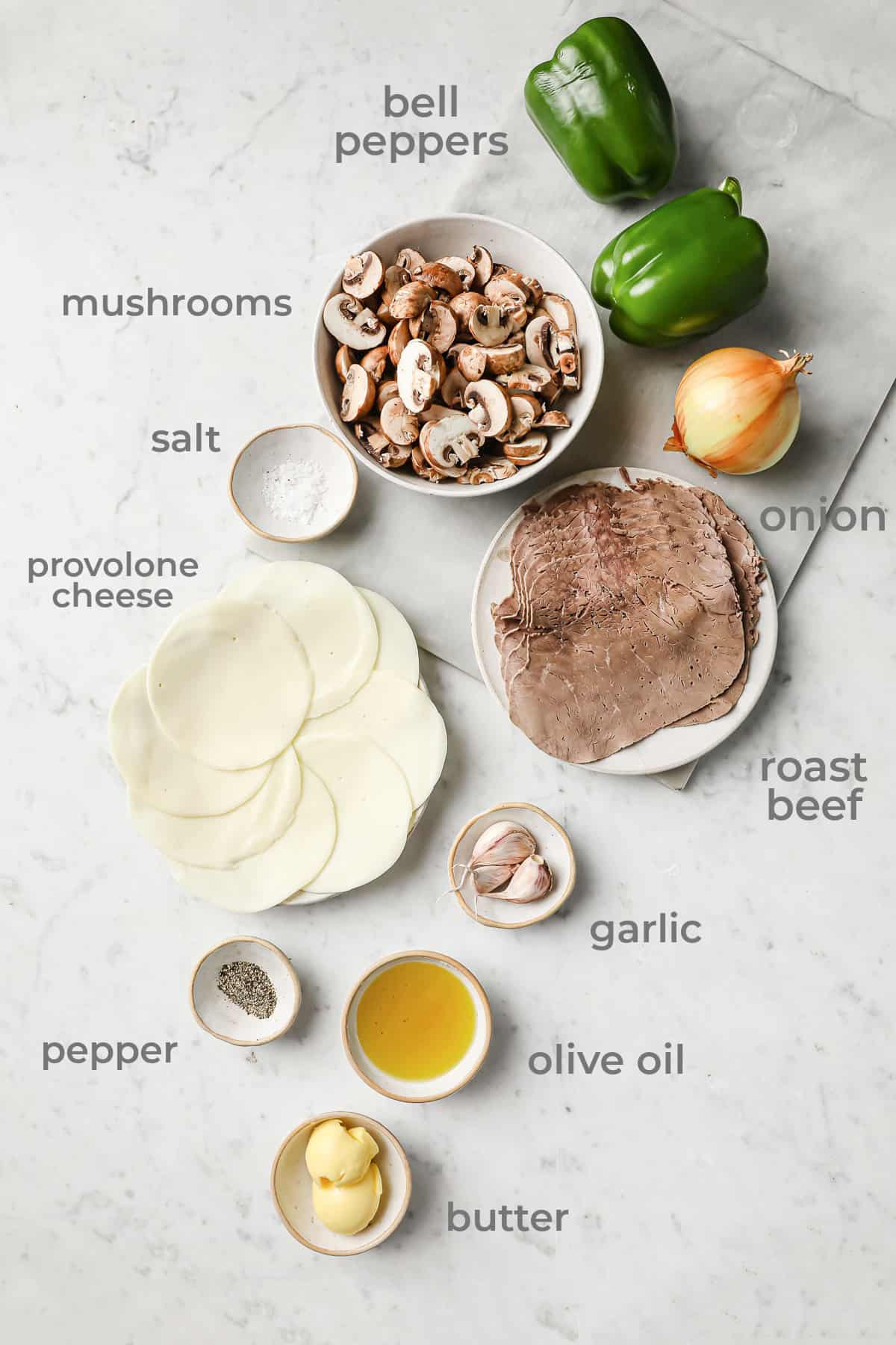 Ingredients to make philly cheesesteak stuffed peppers - roast beef, onion, mushrooms, provolone, garlic