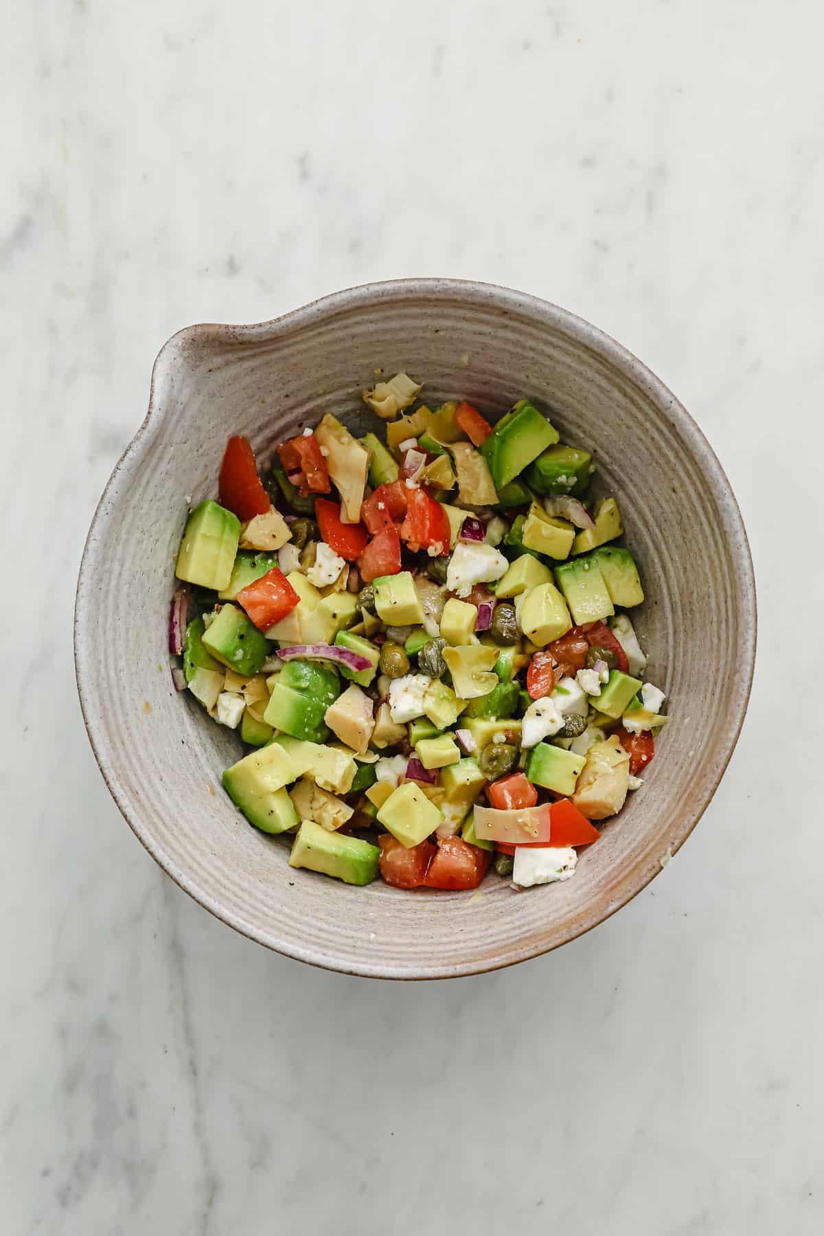 ceramic bowl with avocado salsa with tomatoes, garlic, onion, cilantro, lime juice