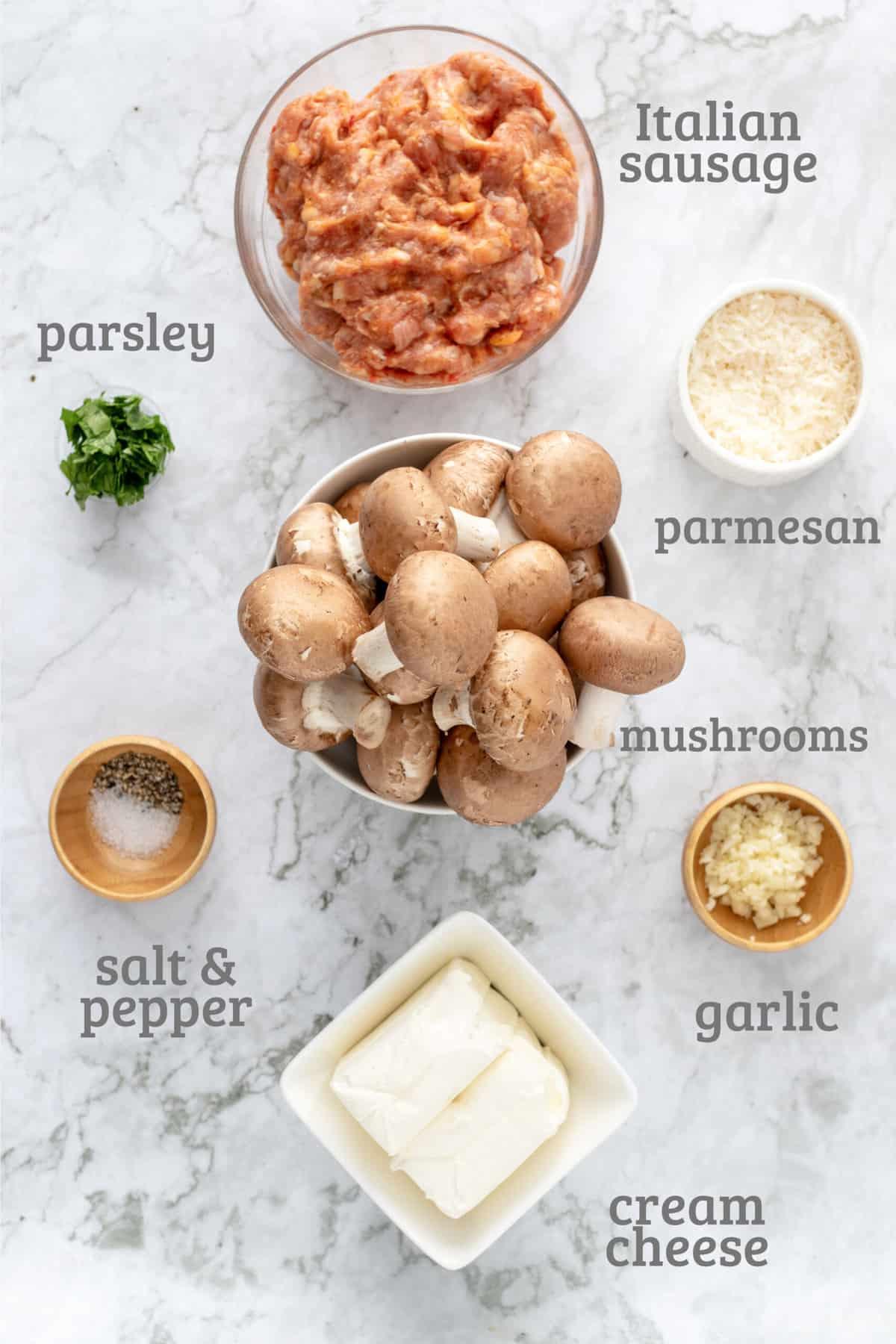 Ingredients for stuffed mushrooms - sausage, parmesan, garlic, mushrooms, cream cheese, salt, and pepper
