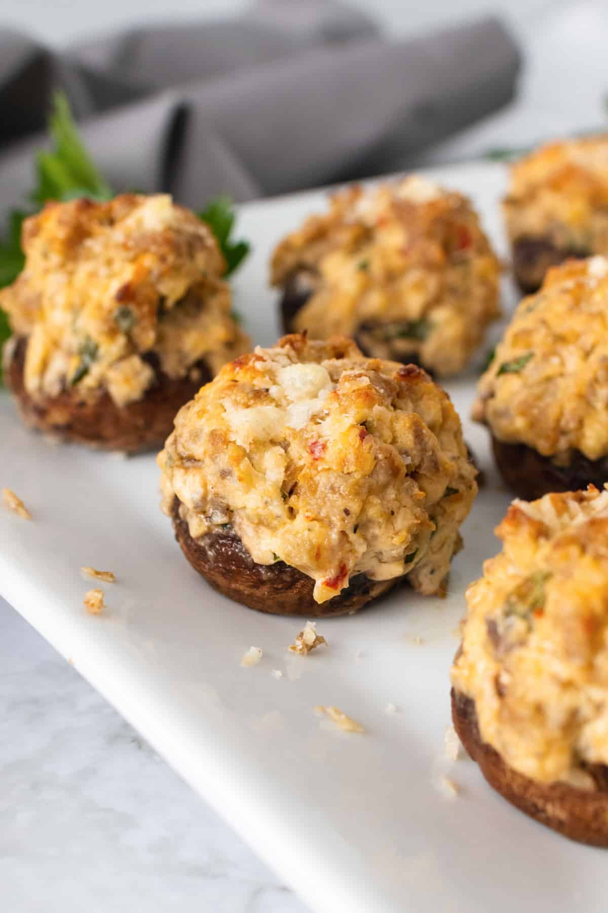 Sausage stuffed mushrooms on a white plate, garnishes with parsley