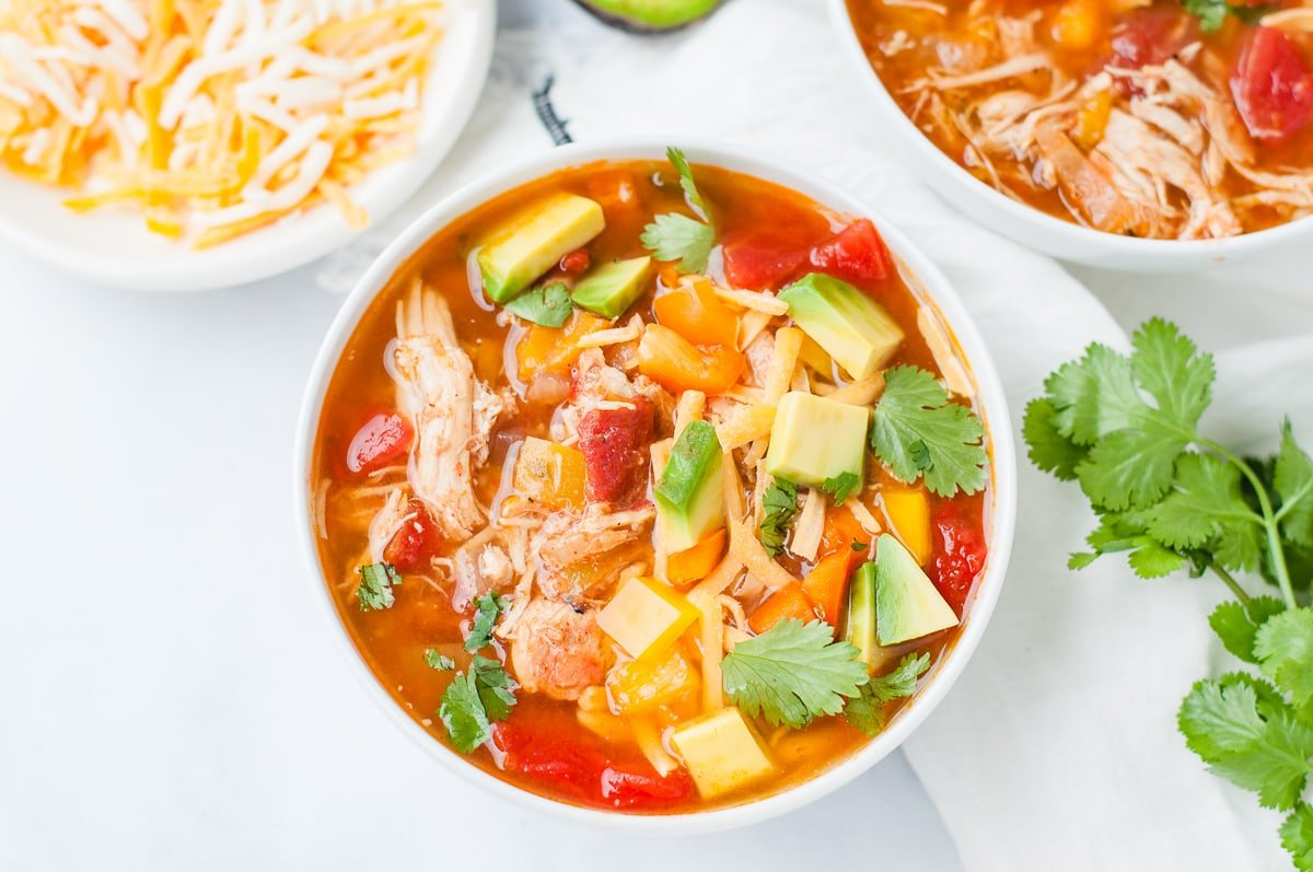 Overhead shot of a bowl of chicken fajita soup, topped with avocado, cilantro, cheese, and bell peppers