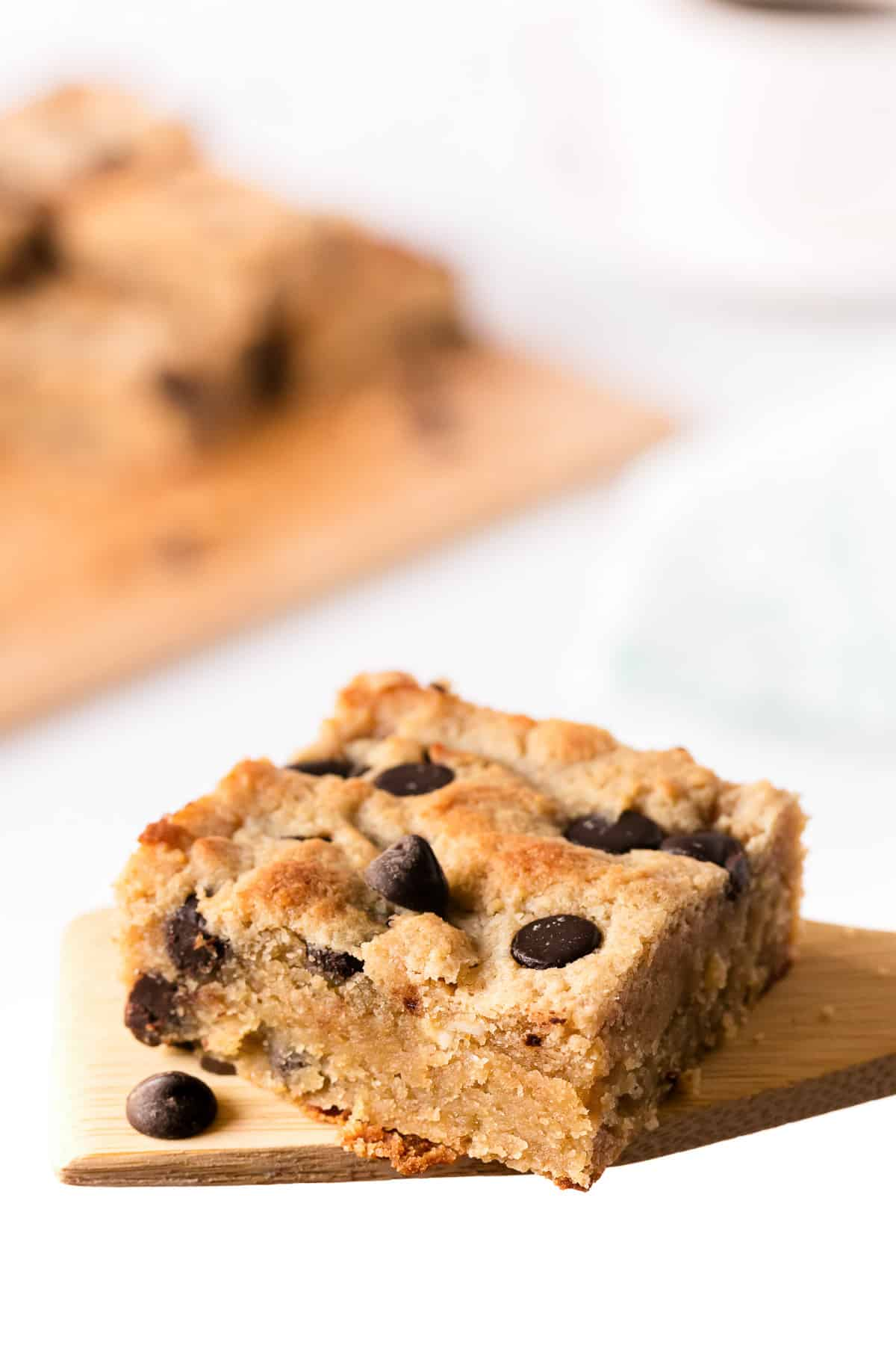 chocolate peanut butter bars stacked on top of each other on parchment paper, with a cup of coffee in the background