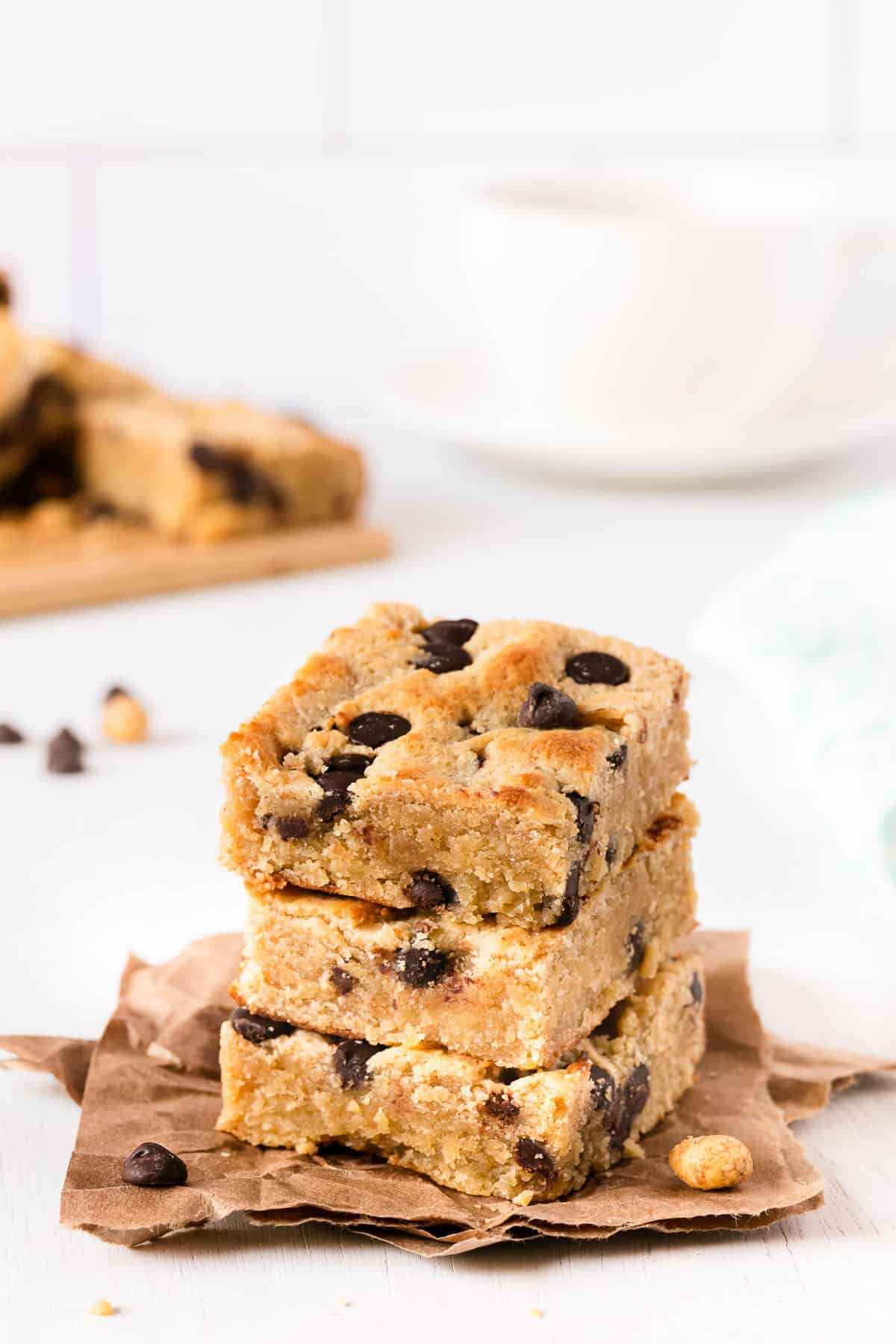 gluten free cookie bars stacked on top of each other on parchment paper, with a cup of coffee in the background