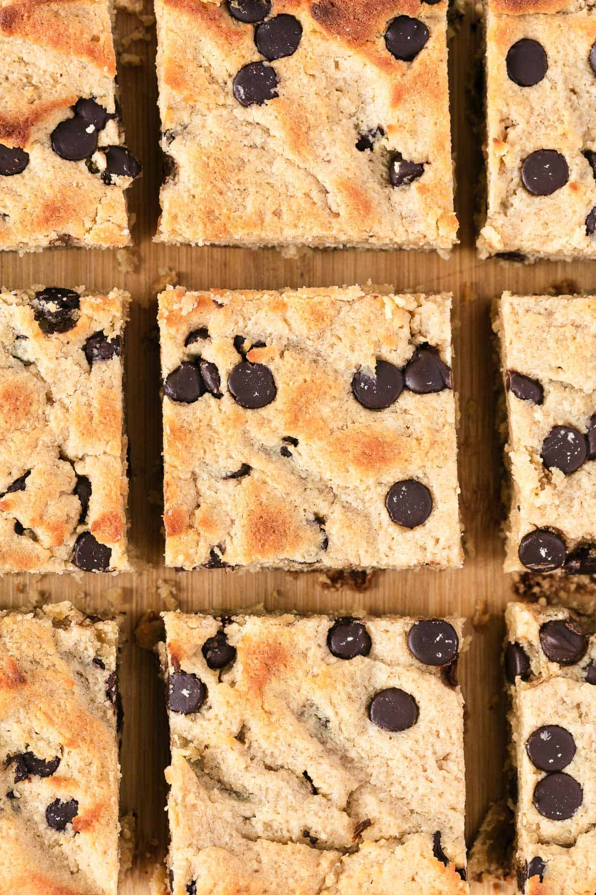 keto blondies stacked on top of each other on parchment paper, with a cup of coffee in the background