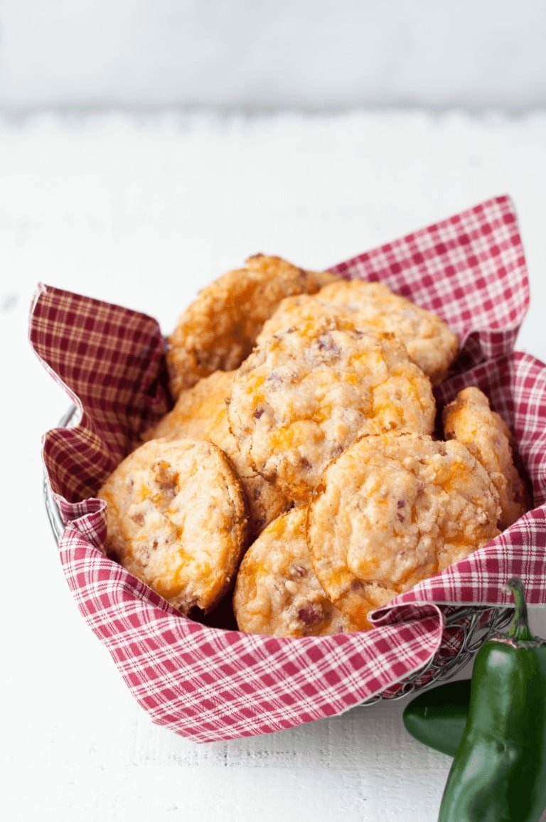 Cheddar Jalapeno Bacon Biscuits piled high in a basket lined with a white and red gingham napkin, sitting on a white wooden countertop with a light gray background and fresh jalapenos in the bottom right corner.