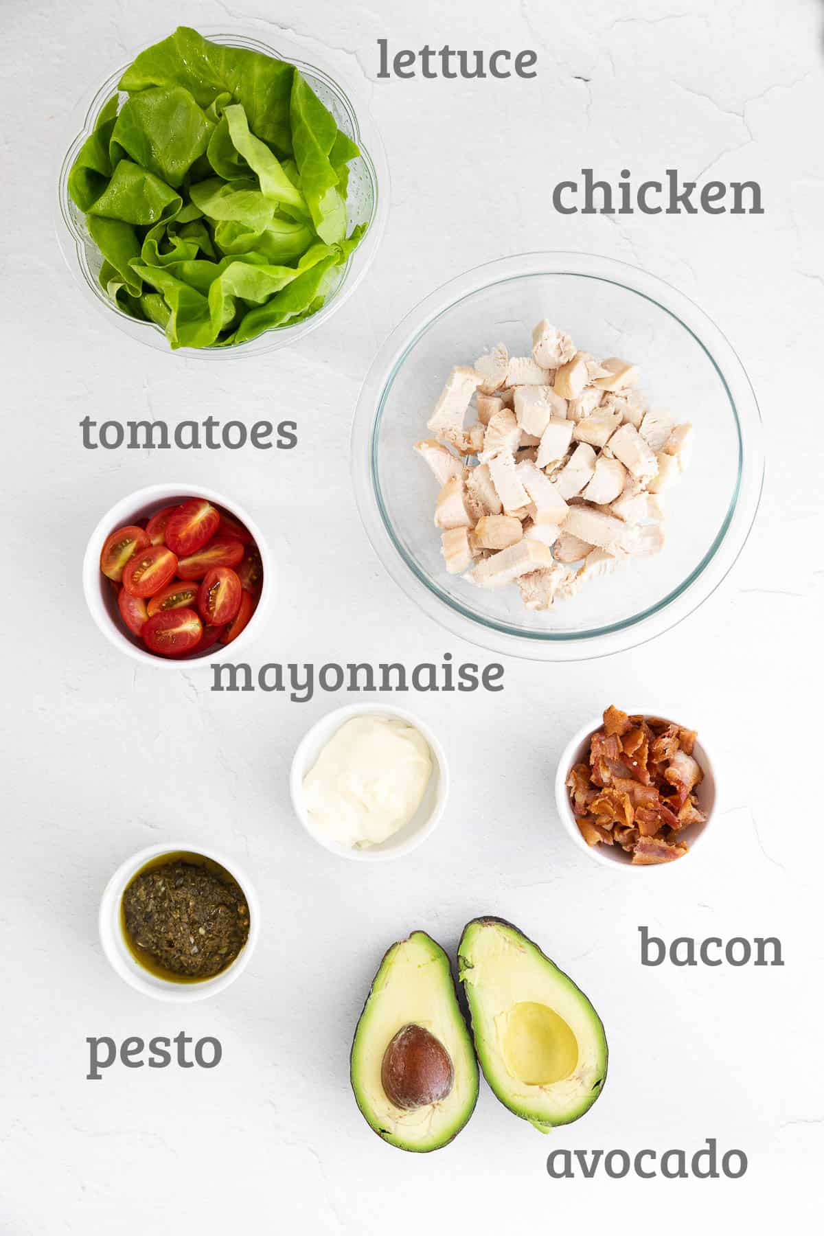Ingredients for pesto chicken salad - chicken, bacon, avocado, tomato, mayonnaise, pesto