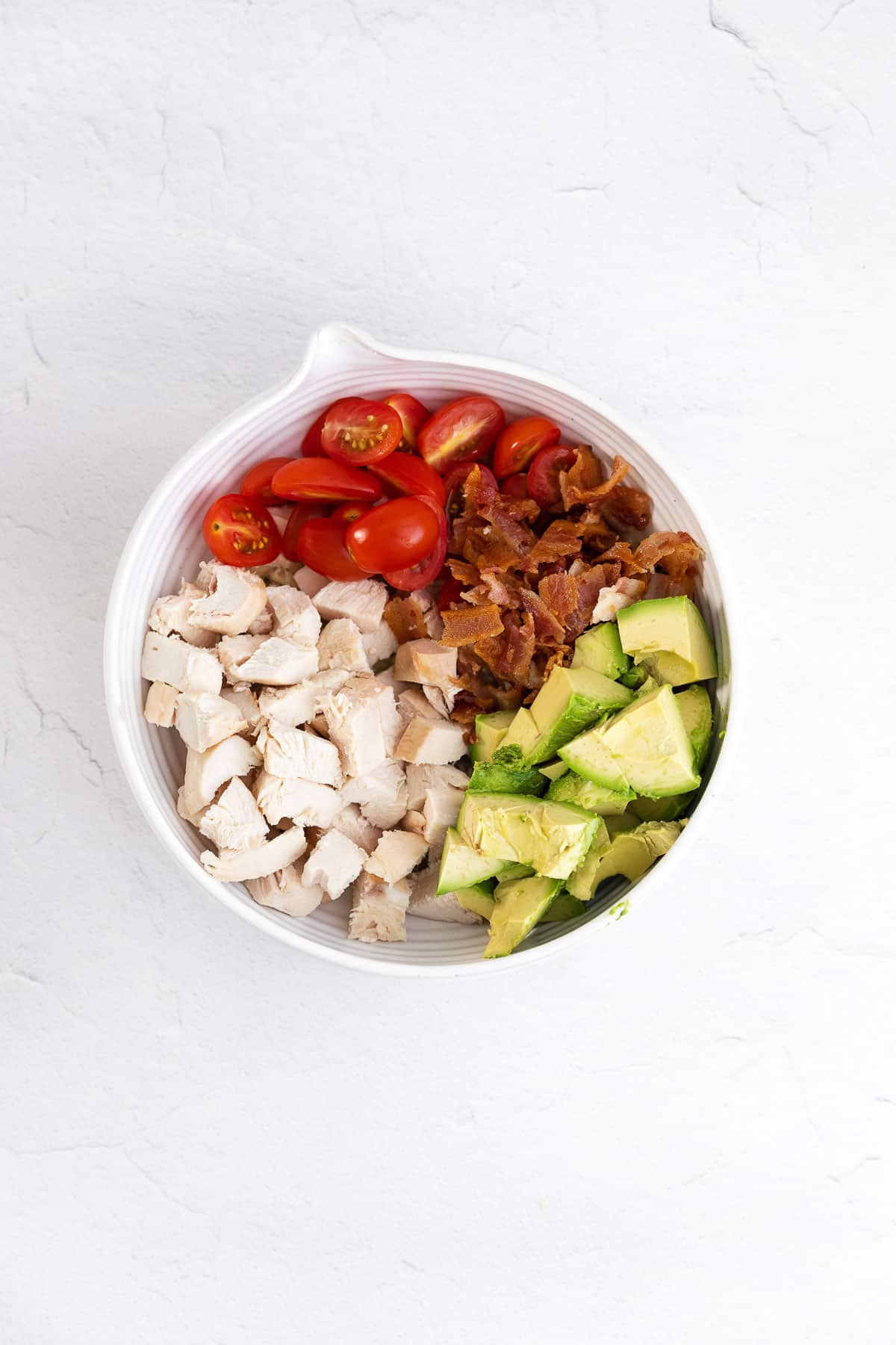 mixing bowl with chopped chicken, avocados, tomatoes, bacon, pesto, and mayo