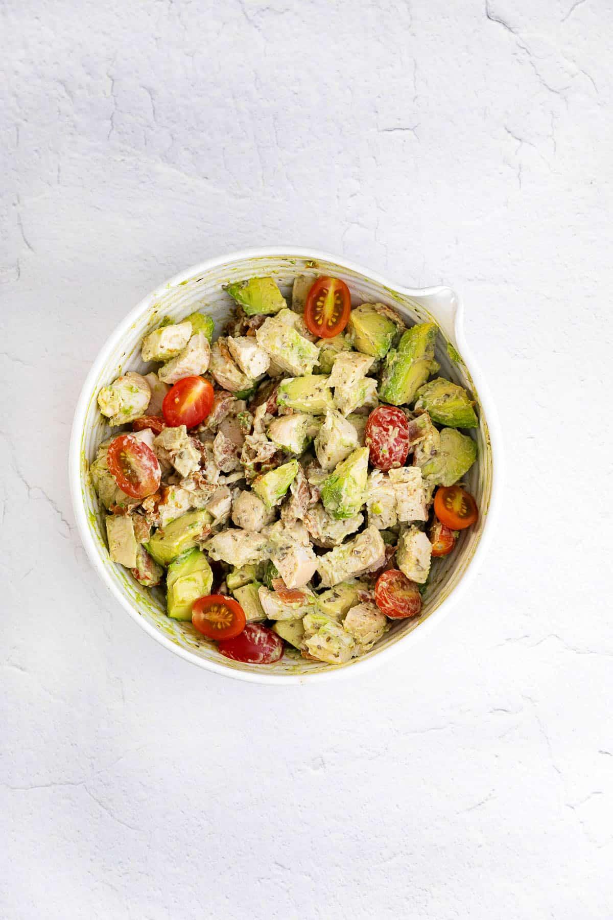 ceramic bowl with pesto chicken salad - pesto, chicken, tomato, avocado, mayo, and pesto