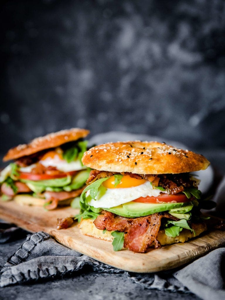 Two bagel breakfast sandwiches are layered with egg, argugula, avocado, tomato, and bacon. The sandwiches sit on a wooden cutting board with a dark gray background.