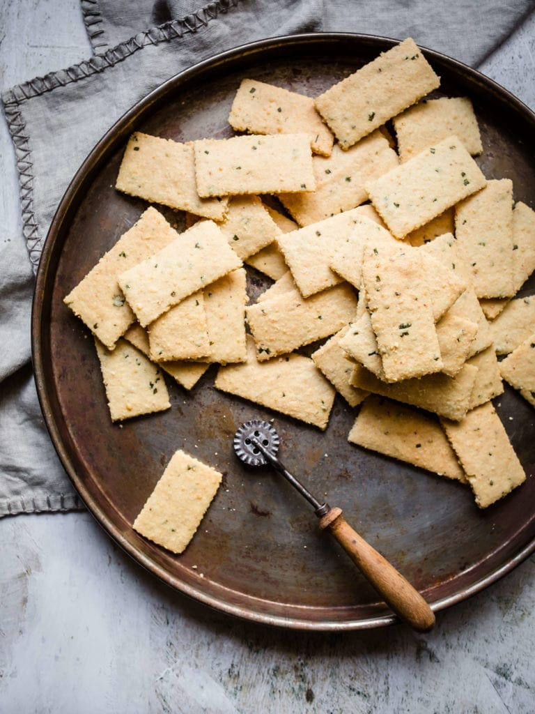 Overhead shot of a pile of freshly baked Parmesan Chive and Garlic keto crackers sits on a metal plate with a pastry cutter. The plate rests on a pile of light gray napkins, all sitting on a white marble countertop.