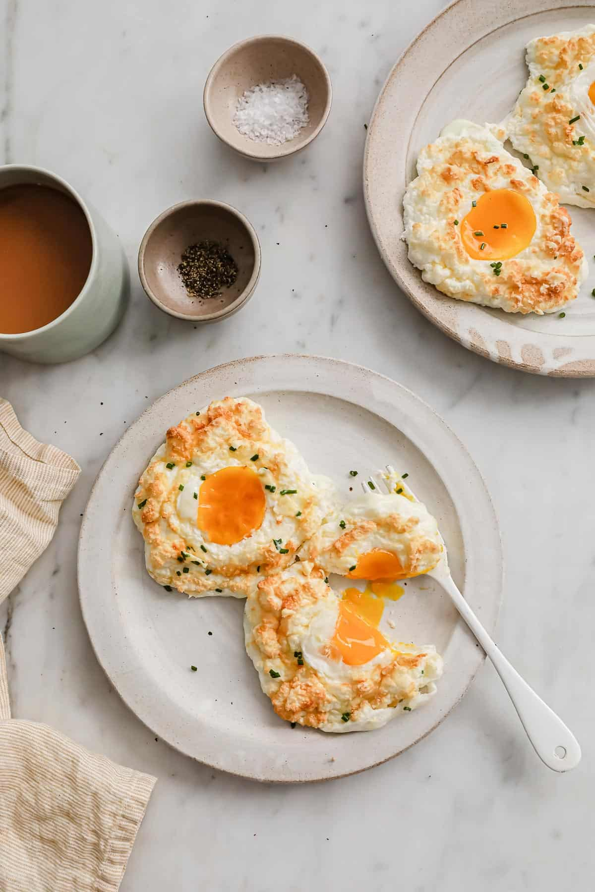 2 baked egg clouds, topped with chives, on a white ceramic plate with a fork