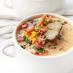 Straight on shot of a piping hot bowl of bacon cheeseburger soup, topped with bacon, cheese, tomatoes, and pickles