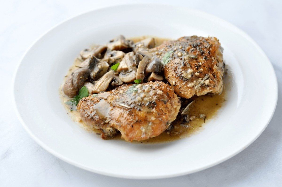 A plate of chicken and mushrooms sautéed with an herby sauce