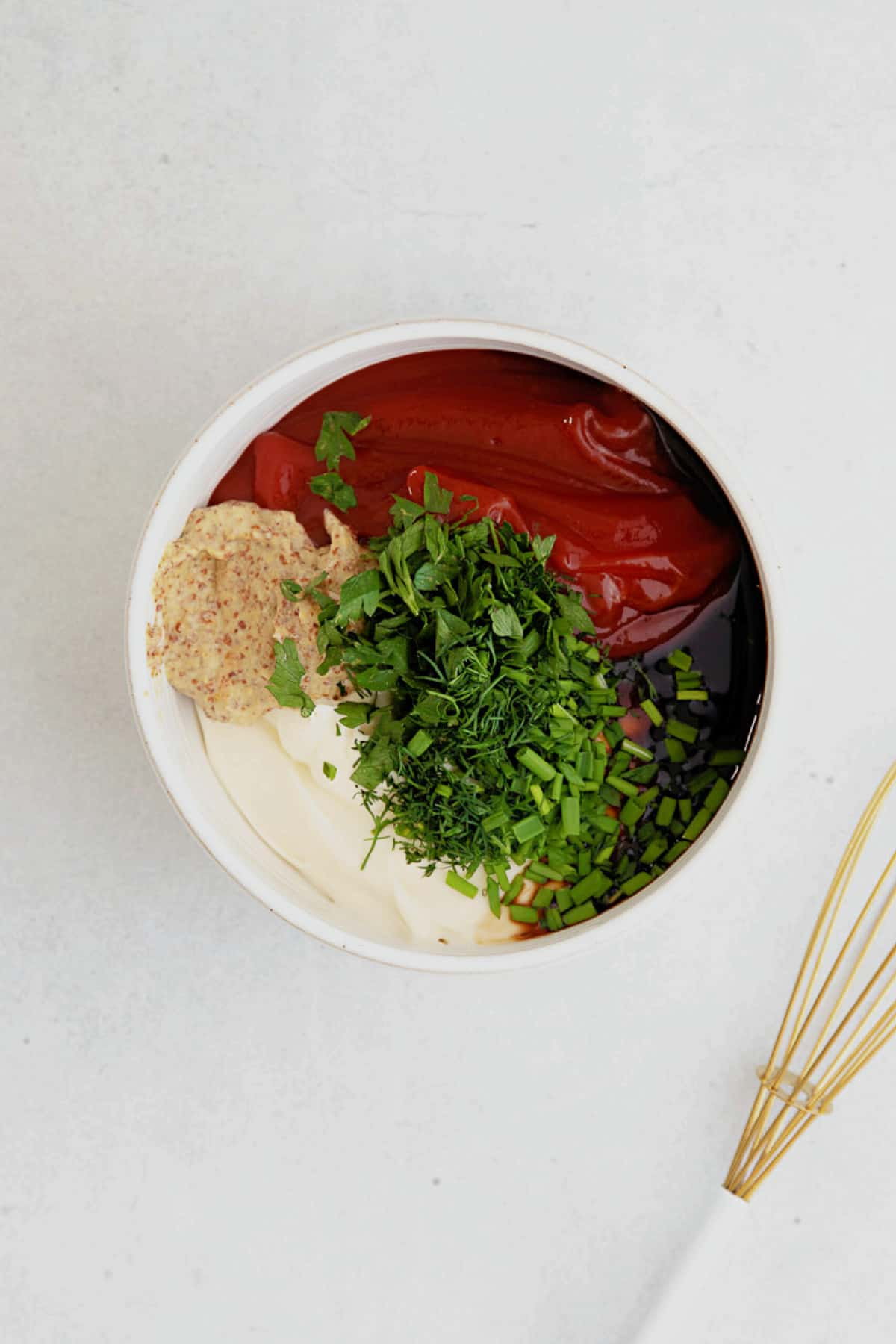 Ingredients for Russian dressing in a white ceramic bowl - ketchup, mayo, dijon, Worcestershire, fresh herbs