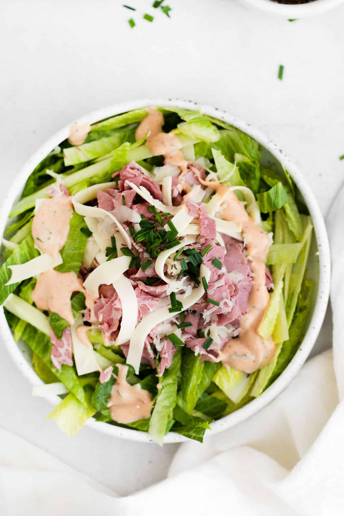 salad in a white ceramic bowl with romaine, corned beef, sauerkraut, Swiss cheese, and Russian dressing