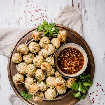 Asian Chicken Meatballs on a bronze plate with tooth picks, fresh herbs, and dipping sauce.
