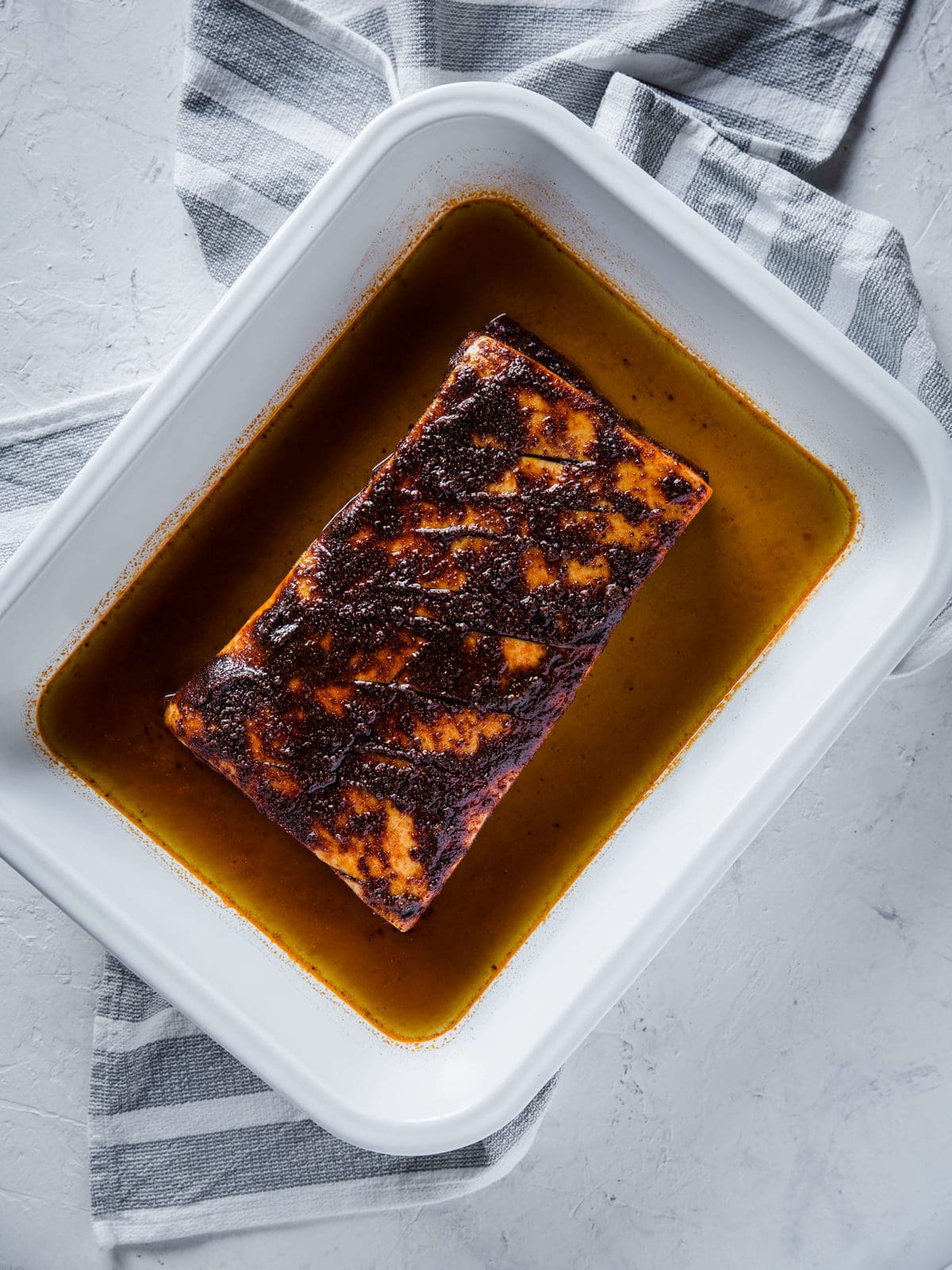 pork belly in a white baking dish, rubbed down with olive oil and coffee barbecue dry rub, surrounded by beef stock