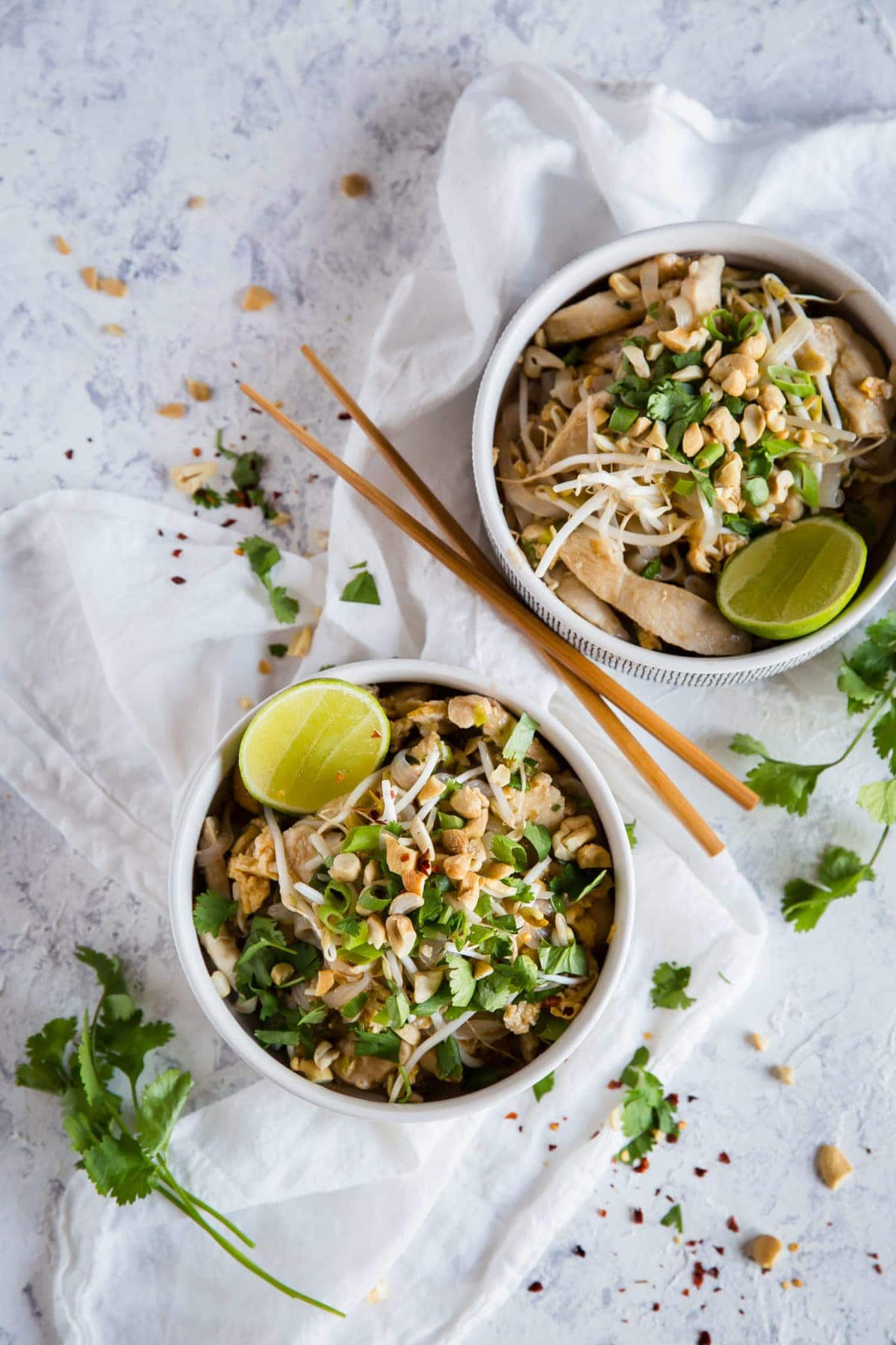 2 white bowls, full of keto Pad Thai, garnished with green onion, peanuts, cilantro and lime wedges and served with chopsticks