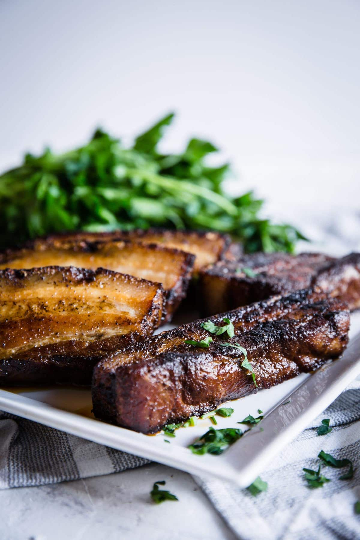 crispy sliced pork belly on a white plate, served with fresh greens