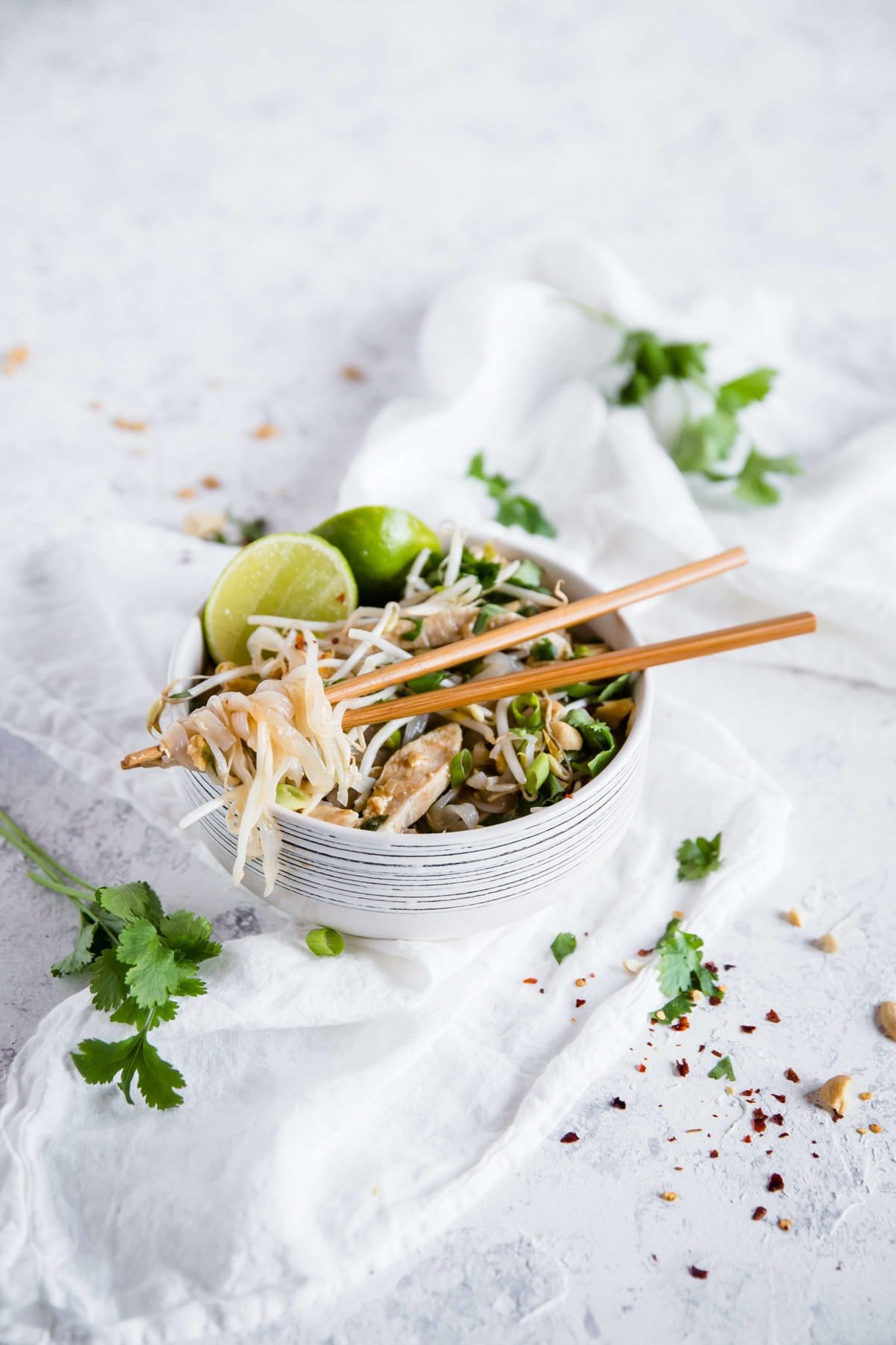 keto Pad Thai, served in a white ceramic bowl with wooden chopsticks and garnished with lime wedges