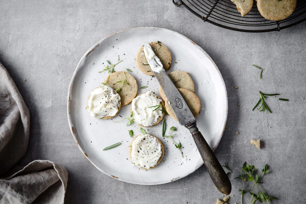 Plate of crunchy keto crackers with cream cheese spread on top