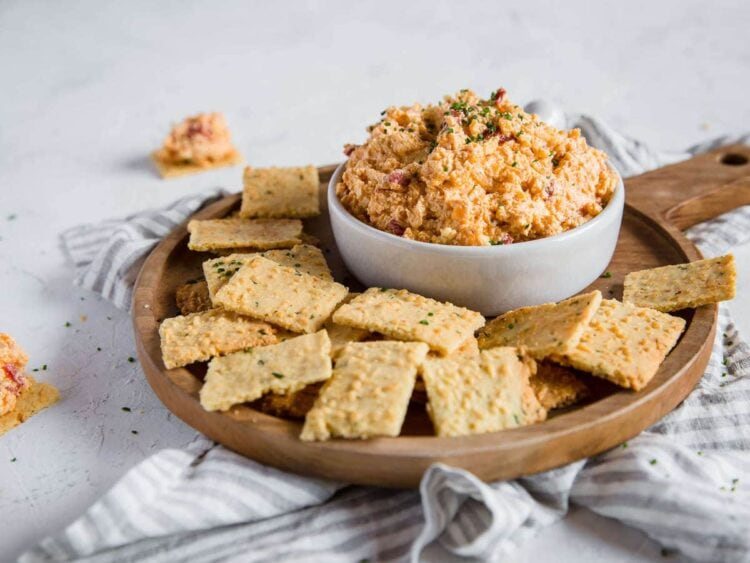 A head on shot of a cheese dip dish overflowing with Pimento Cheese Dip, sitting on a wooden charcuterie board piled with Parmesan Chive and Garlic Keto Crackers.