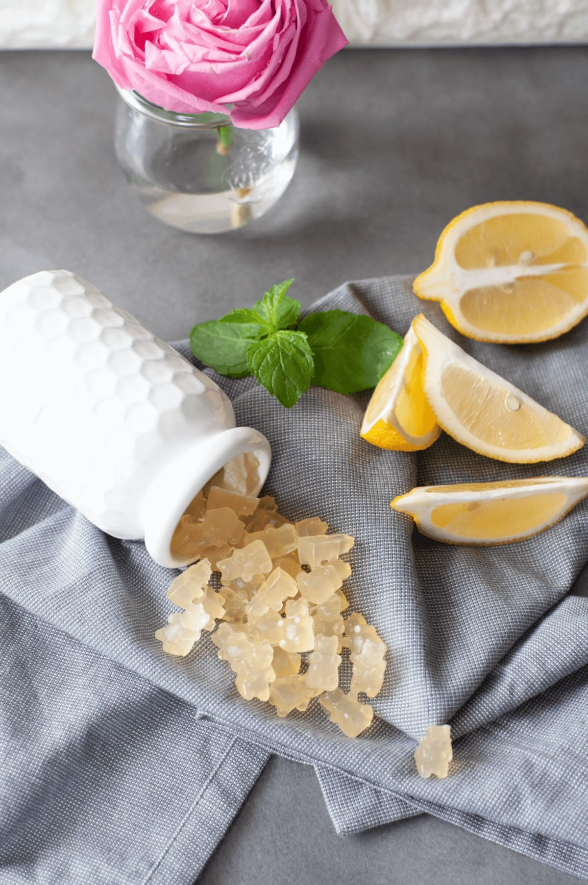 Fresh mint and lemons next to a white jar, spilling out lemon gummy bears onto a gray napkin.