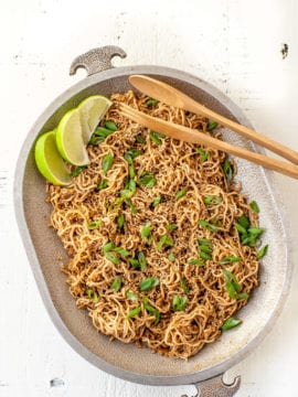 sesame ginger noodles, topped with green onions, sesame seeds and lime wedges, served on a large platter