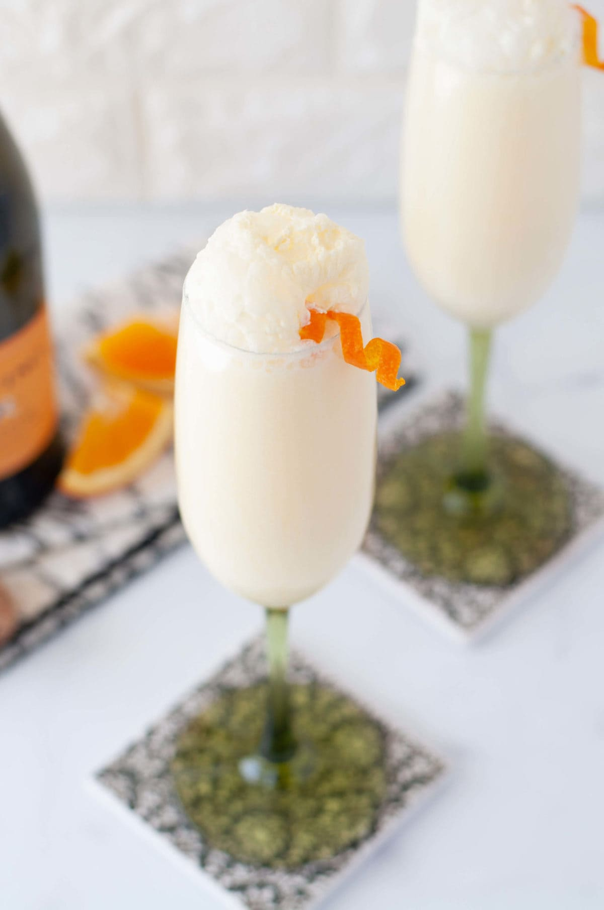 a close up shot of a frothy creamsicle mimosa with an orange twist