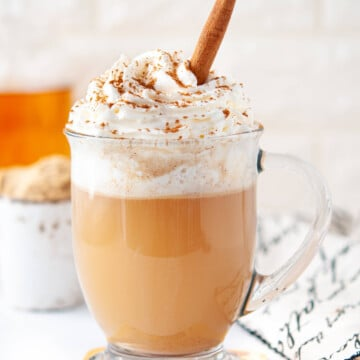 keto hot buttered rum cocktail in a clear glass mug, topped with whipped cream and a cinnamon stick