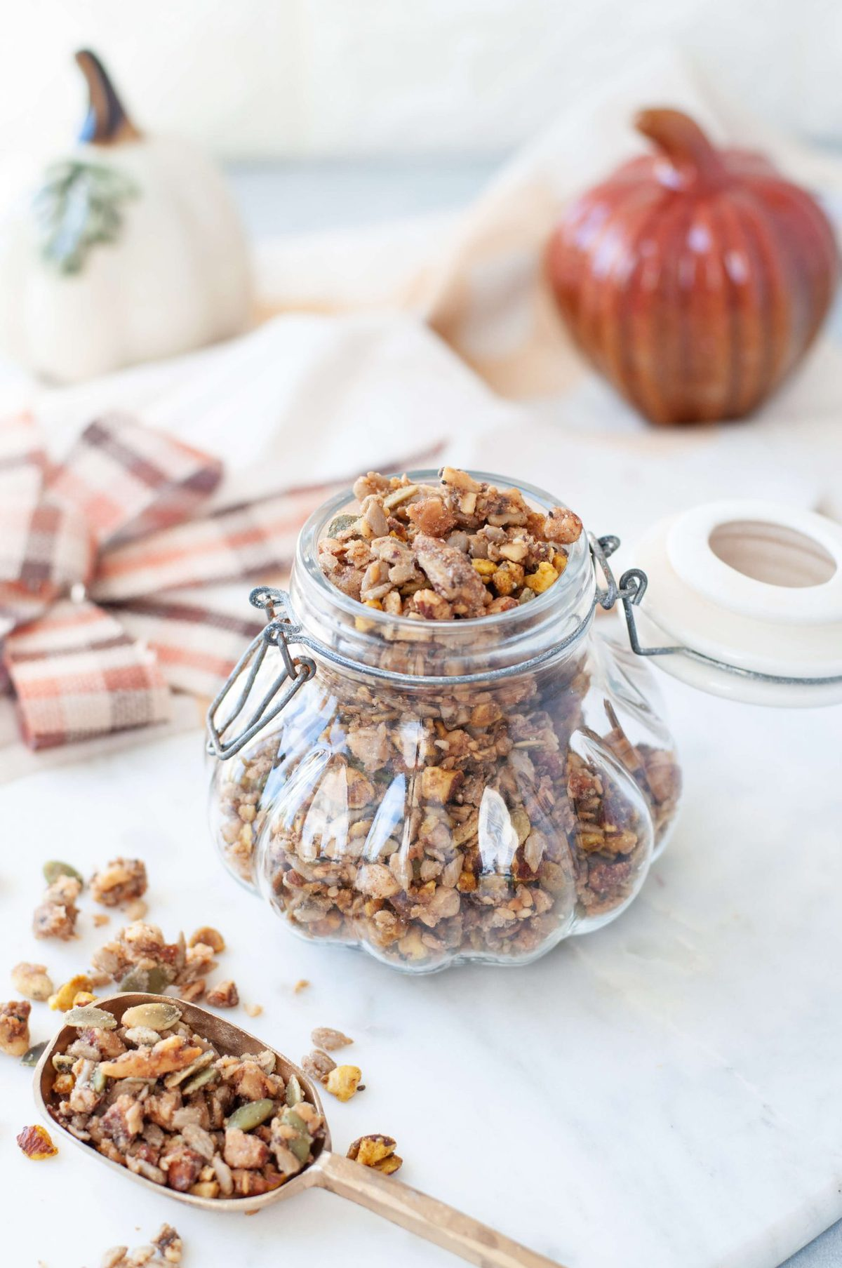 Gluten Free granola in a decorative glass jar, shaped like a pumpikin