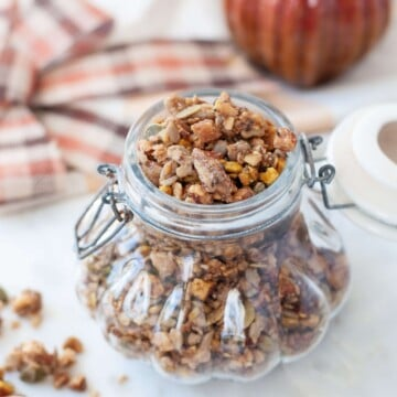Gluten Free Pumpkin Spice granola in a decorative glass jar, shaped like a pumpikin