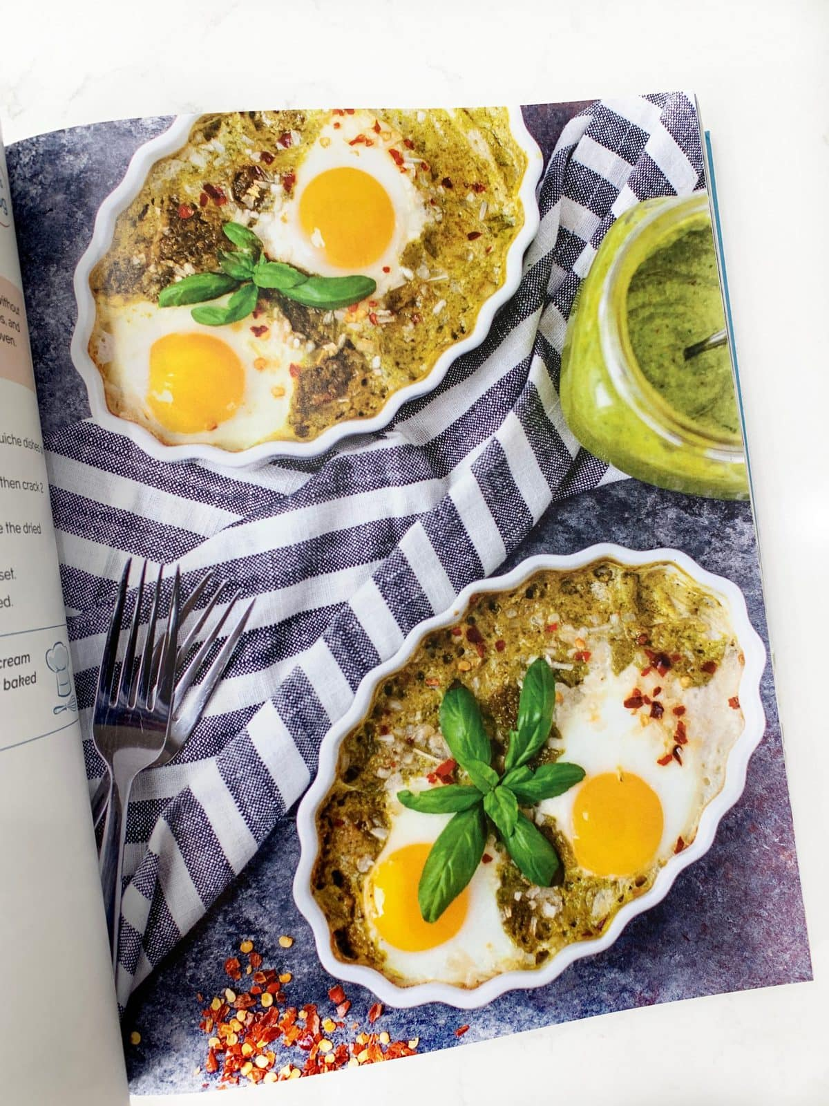 flat lay of a breakfast recipe in a cookbook - pesto baked eggs