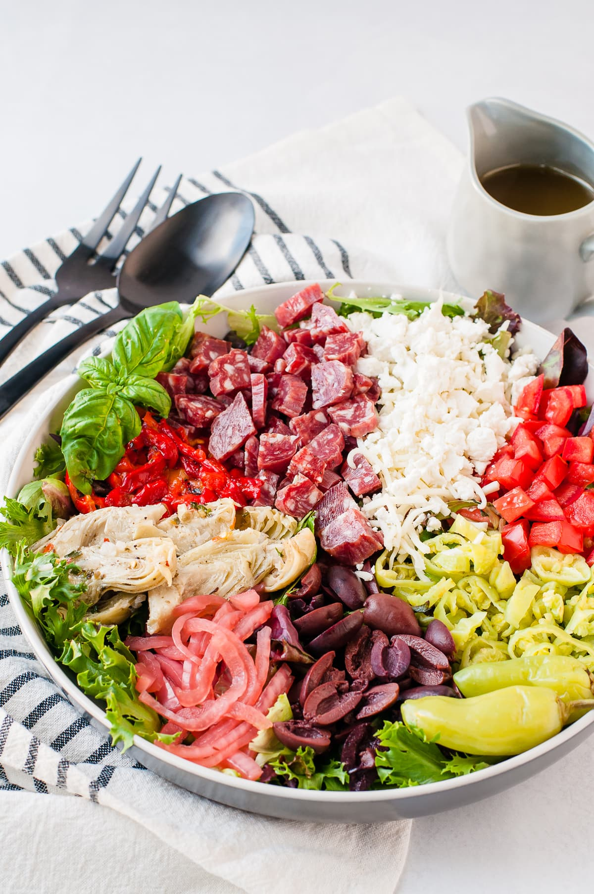 Overhead shot of a brightly colored antipasto salad - topped with meats, cheese, and vegetables