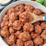 Overhead shot of slow cooked meatballs in tomato sauce. surrounded by fresh ingredients