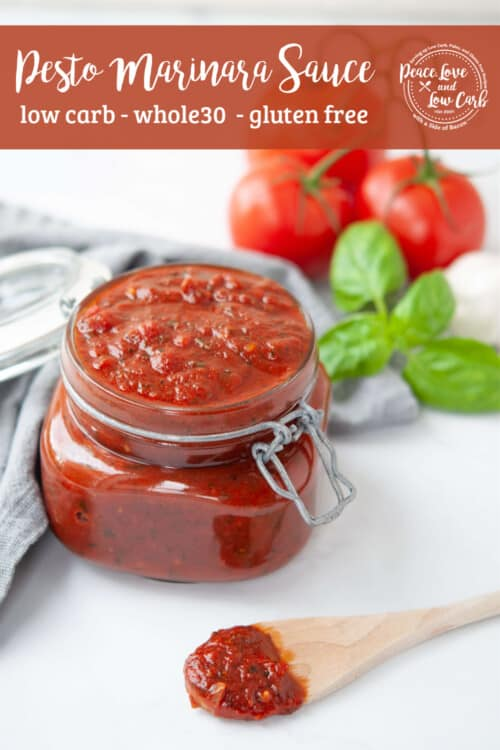 jar of homemade marinara sauce with fresh tomatoes and basil in the background
