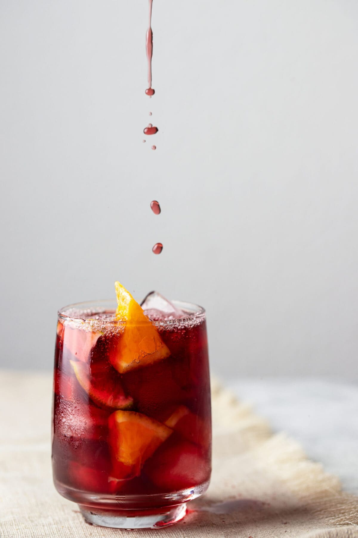 Refreshing glass of kombucha Sangria on cement background.