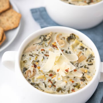Bowl of spinach and artichoke soup in a white bowl, topped with shaved parmesan cheese and red pepper flakes