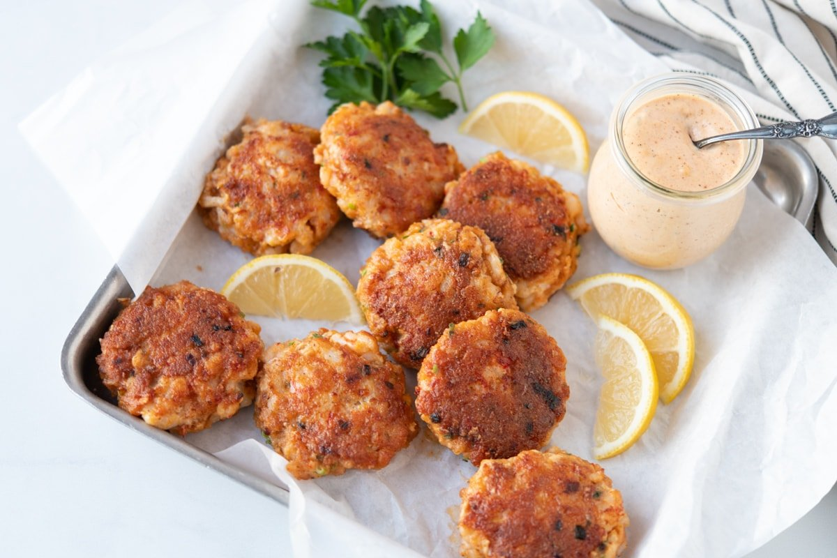 Shrimp cakes surrounded by lemons and parsley, served with remoulade