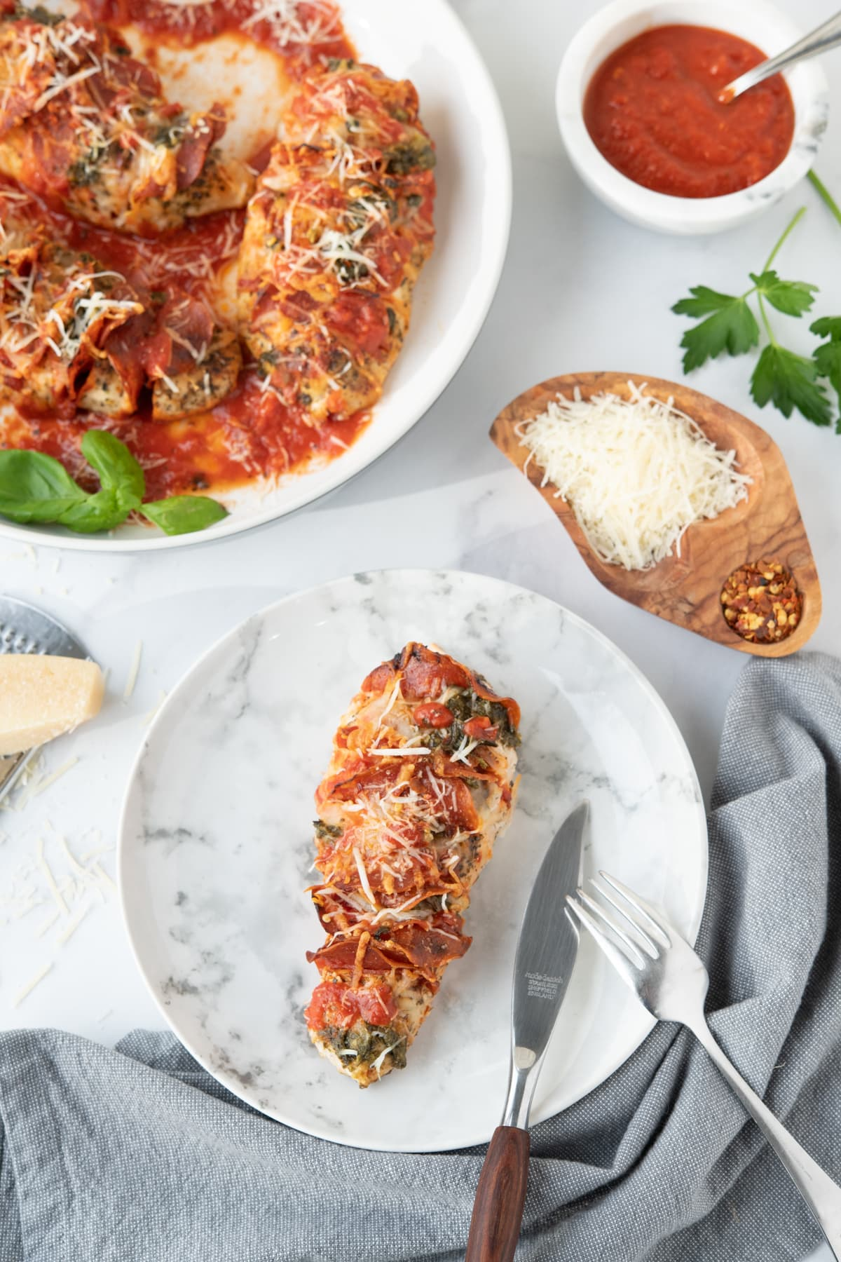Chicken breasts with pepperoni, pizza sauce and cheese, garnished with cheese, pesto and basil in a white dish