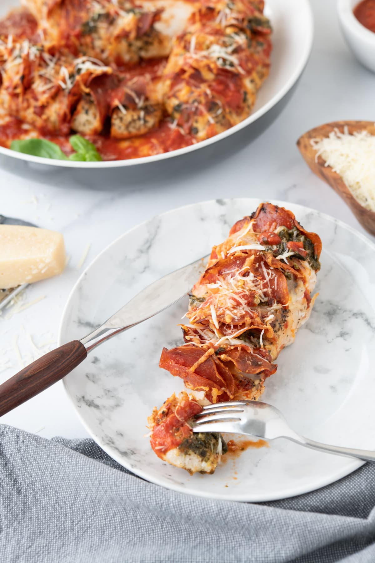 Chicken breast with pepperoni, pizza sauce and cheese, garnished with cheese and pesto, on a marble plate with a fork and knife