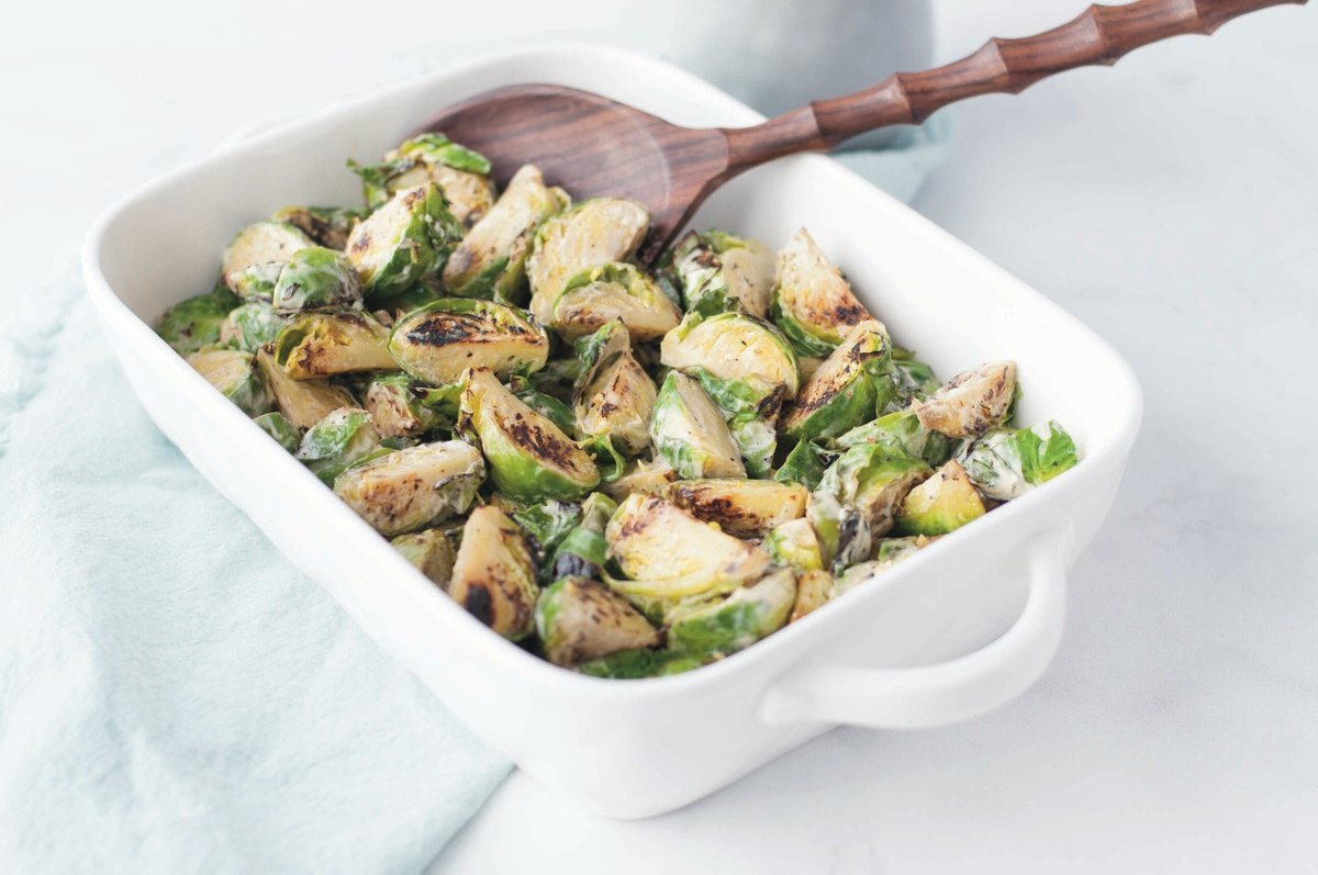 White baking dish full of Roasted Brussels sprouts, with a wooden serving spoon