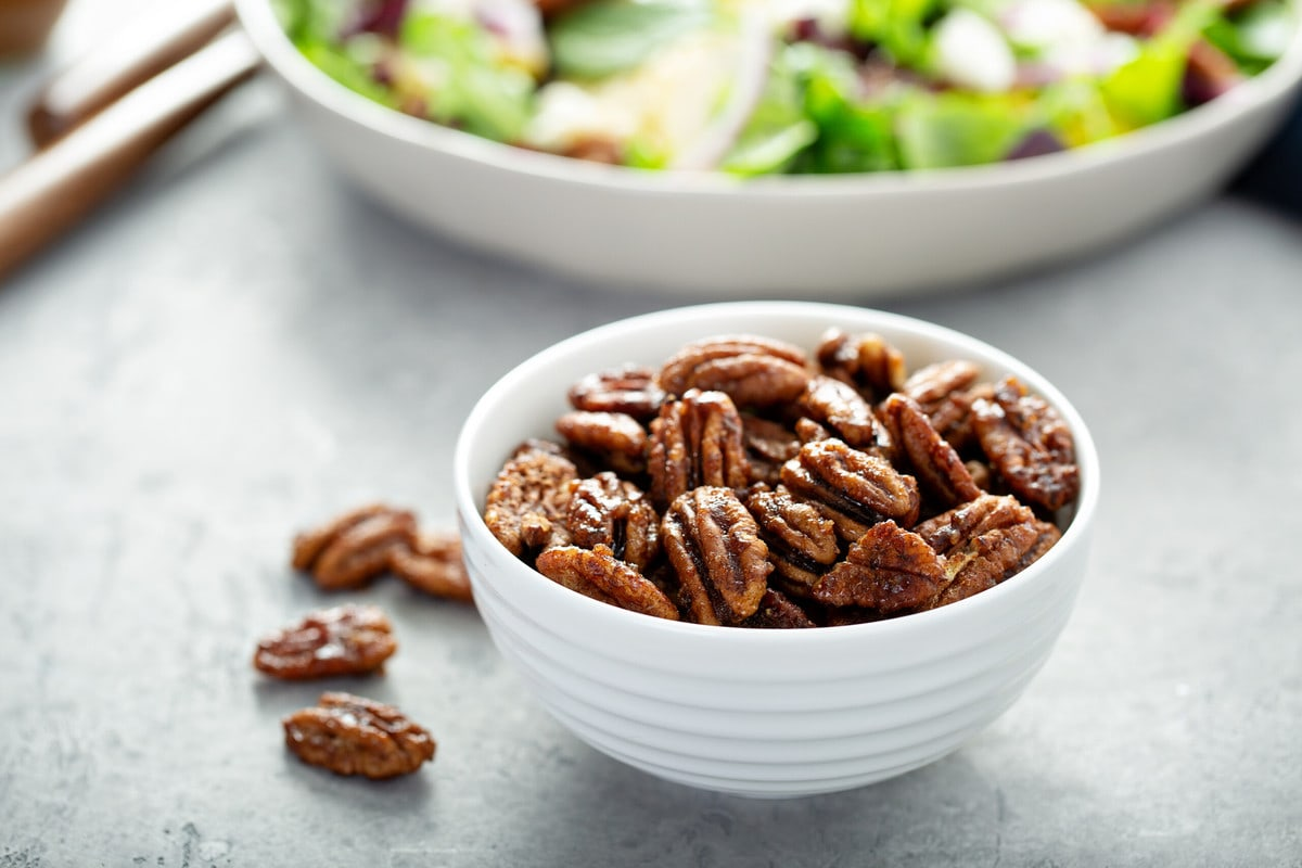 low carb candied pecans in a white bowl, with a salad in the background