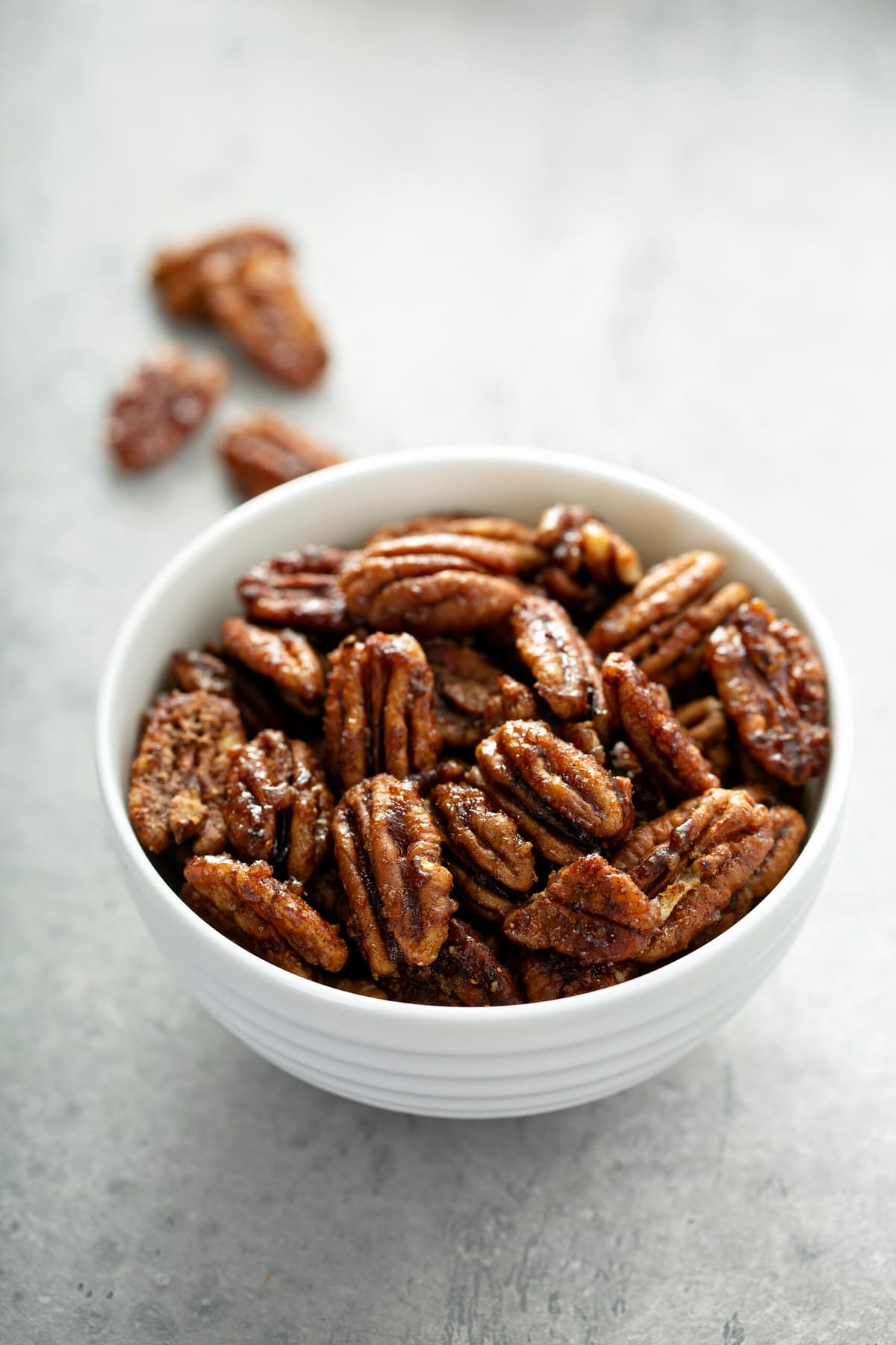 candied pecans in a white bowl on a concrete surface