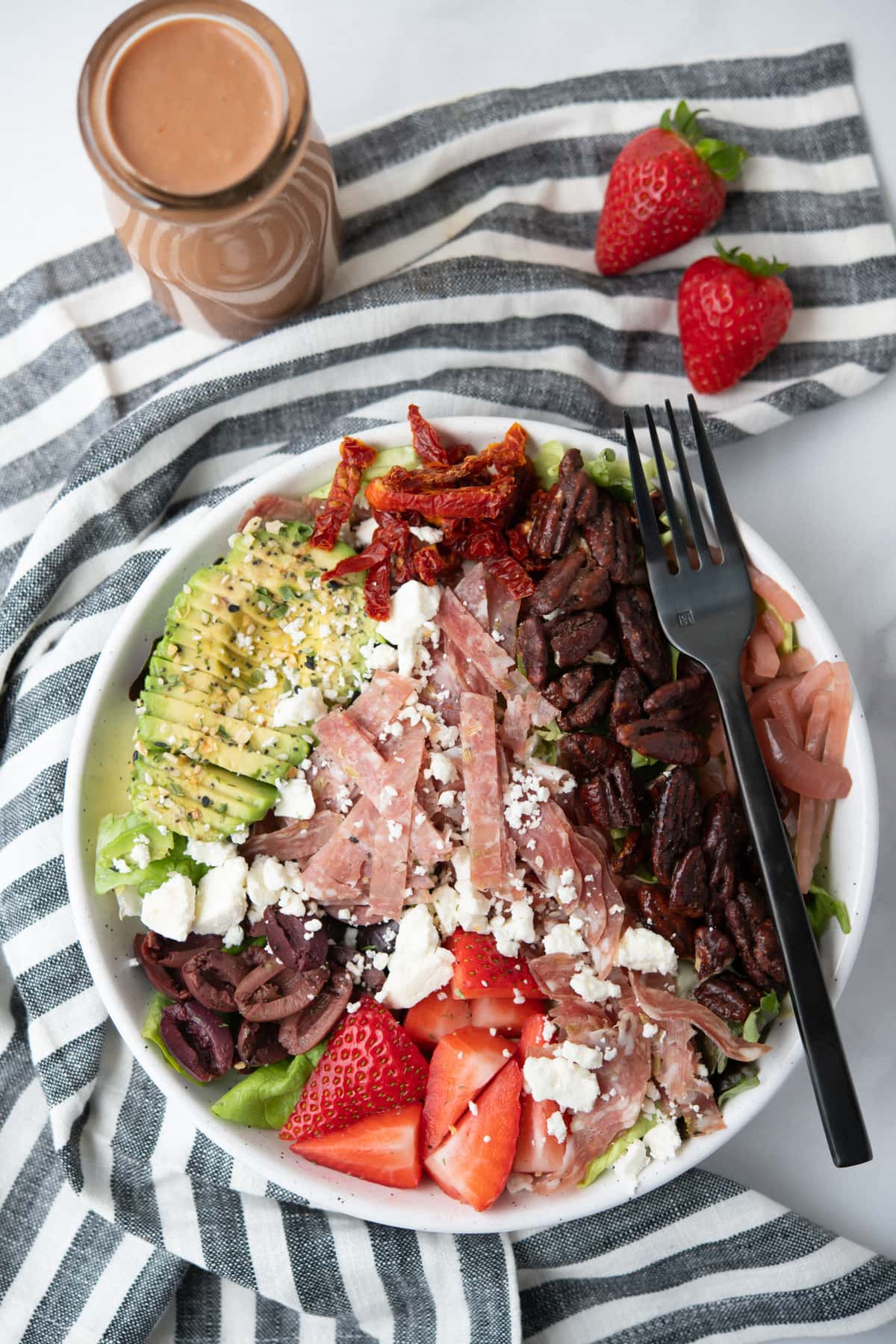 Overhead shot of a colorful salad with avocado, salami, cheese, pecans, and strawberries