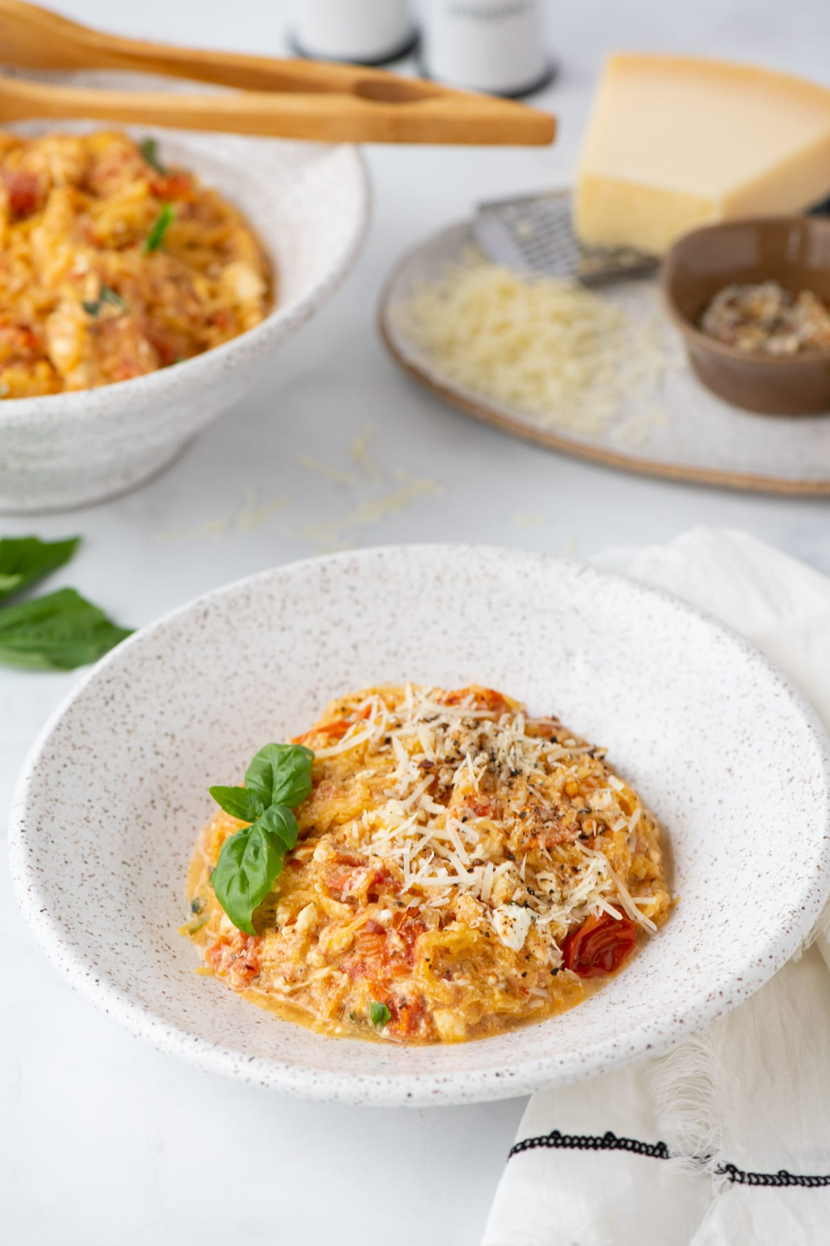 A specked pottery bowl filled with a low carb baked feta pasta with tomatoes, basil and topped with cheese