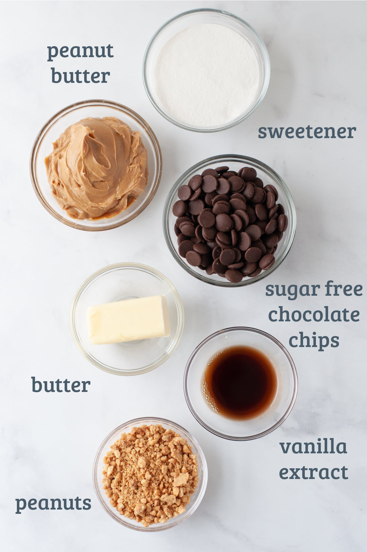 Ingredients arranged in individual ramekins - peanut butter, sweetener, chocolate chips, butter, peanuts, and vanilla extract